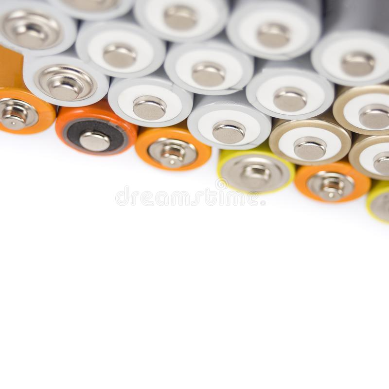 Alkaline batteries multi-colored metal and the positive side of the AA-size batteries isolated on white background closeup stock image