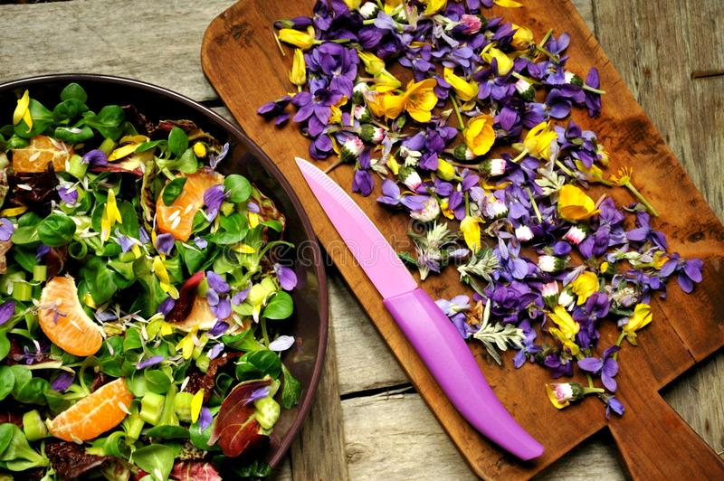 Alkaline, healthy food: salad with flowers, fruit and valerian salad stock image