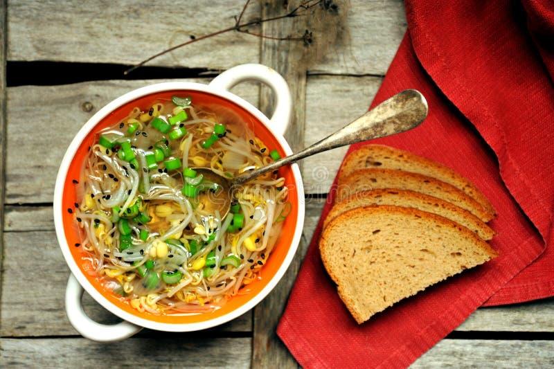 Alkalische, gezonde maaltijd: de soep en het brood van de sojabonenspruit stock fotografie