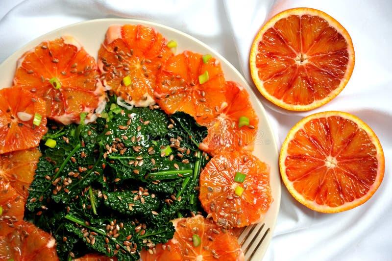 Alkalisk sund mat: grönkål och röd blodapelsinsallad royaltyfria foton