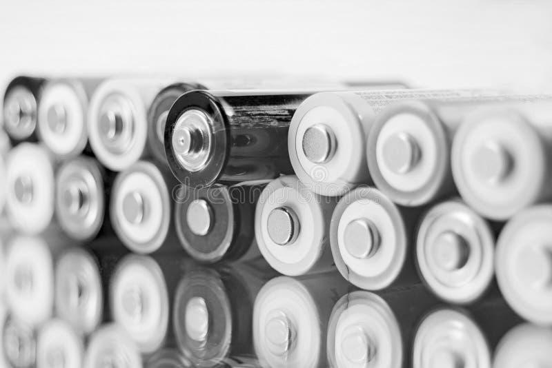 alkaliska AA-batterier på glasytan med reflexbeläggning, saltbatterier, ackumulatorer royaltyfri bild