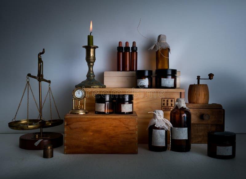 Alkemilabb flaskor krus, våg, stearinljus på trähyllor arkivbilder