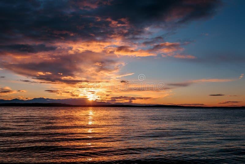 Alki与奥林匹克范围现出轮廓的和水反射的海滩日落 n 免版税库存照片