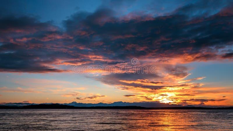 Alki与奥林匹克范围现出轮廓的和水反射的海滩日落 n 库存图片