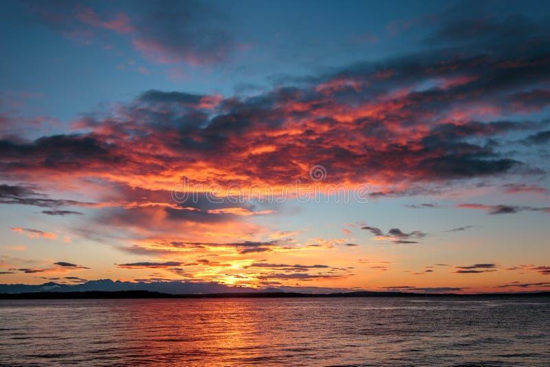 Alki与奥林匹克范围现出轮廓的和水反射的海滩日落 n 免版税库存图片