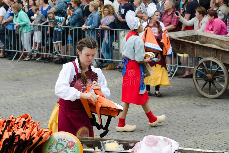 Girls in Traditional Dutch dress work at the Alkmaar cheese market, Netherlands stock images