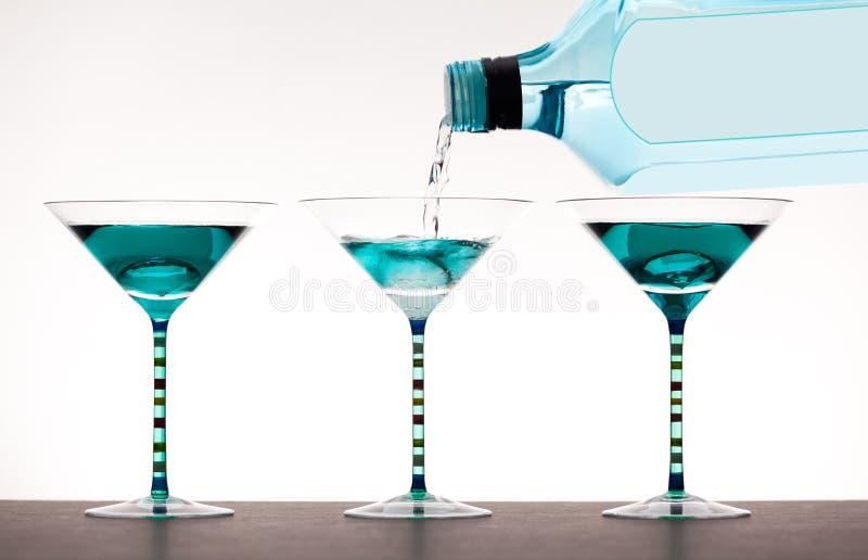 Alkohol, der in Martini-Gläser gegossen wird stockbilder