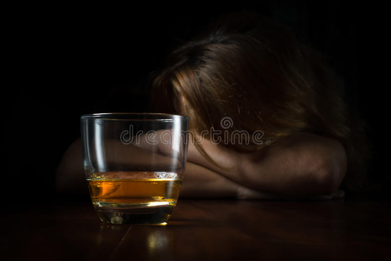 Alkohol missbrukade kvinnan med ett exponeringsglas av whisky royaltyfri bild