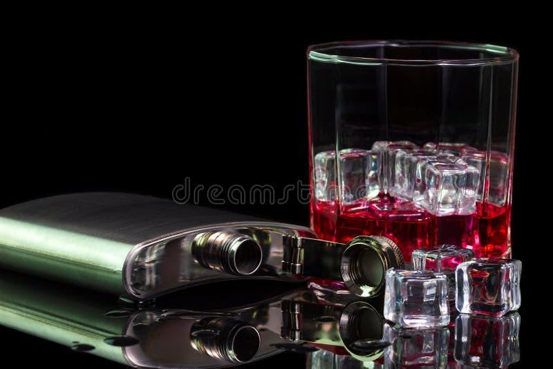 Alkohol och is för rostfritt stålflaskastarksprit på tabellen med röd whisky i exponeringsglas royaltyfri fotografi