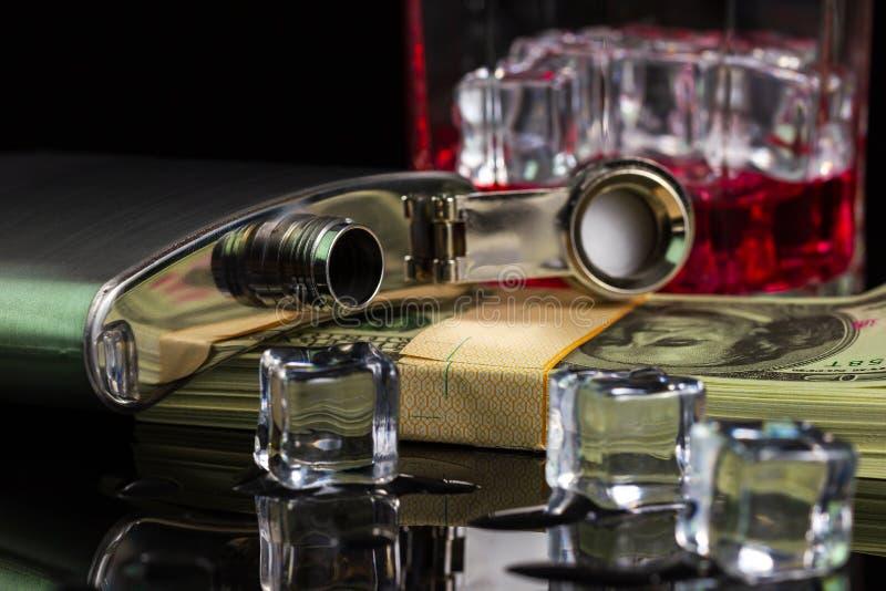 Alkohol och is f?r rostfritt st?lflaskastarksprit p? tabellen med exponeringsglas p? dollarsedel i m?rkerbakgrund arkivbild