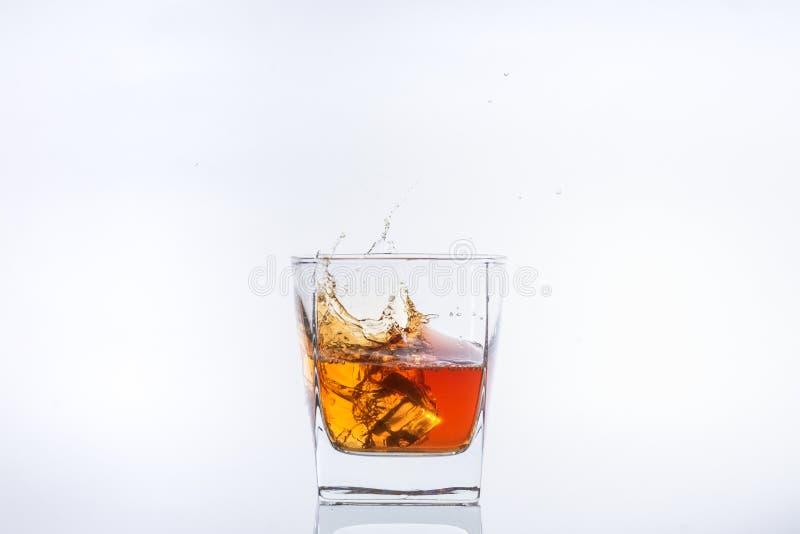 Alkohol w szkle Kostka lodu spada w szk?o z plu?ni?ciami pojedynczy bia?e t?o zdjęcie royalty free