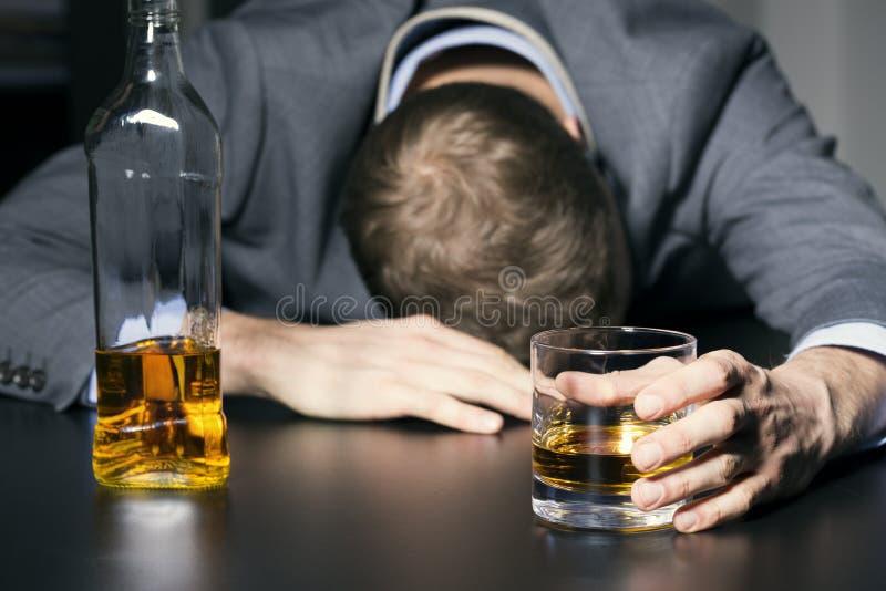 Alkoholböjelse - berusad affärsman som rymmer ett exponeringsglas av whisky arkivfoto