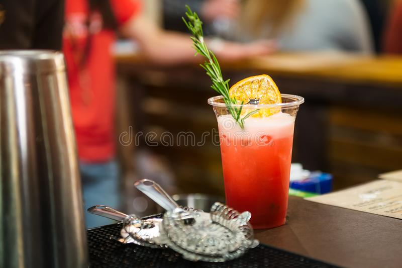 Alkoholcocktailglas auf Barzähler Neues coctail auf einem Farbhintergrund im Plastikglas mit Prostangenmaterial Trinkende Cocktai lizenzfreie stockfotografie