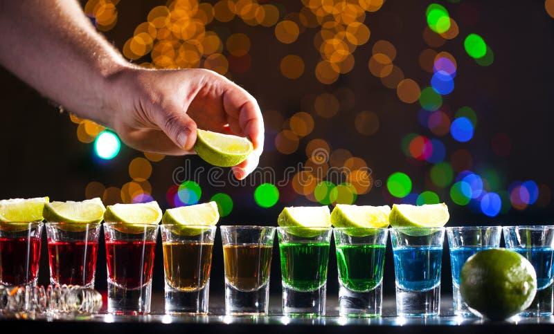 Alkoholdryck in i små exponeringsglas på stång Färgrika coctailar på stången fotografering för bildbyråer
