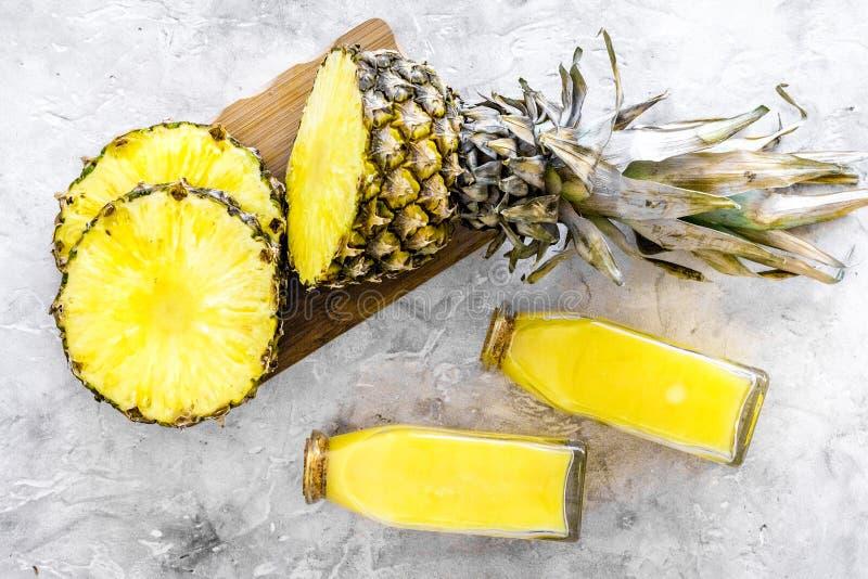 Alkoholfreie Getränke Flasche mit Fruchtsaft nahe Ananasscheiben auf Draufsicht des grauen Hintergrundes lizenzfreies stockfoto