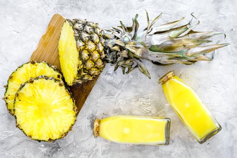 Alkoholfreie Getränke Flasche mit Fruchtsaft nahe Ananasscheiben auf Draufsicht des grauen Hintergrundes lizenzfreies stockbild