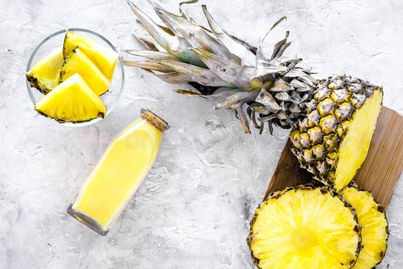 Alkoholfreie Getränke Flasche mit Fruchtsaft nahe Ananasscheiben auf Draufsicht des grauen Hintergrundes stockbilder