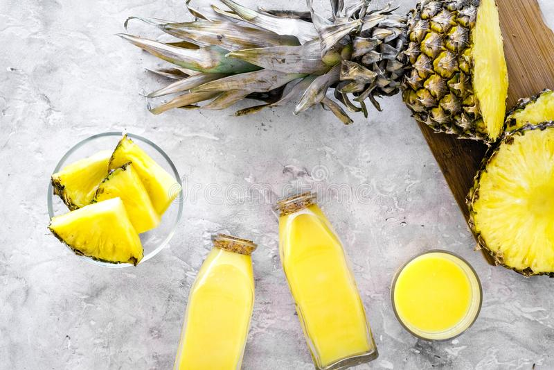 Alkoholfreie Getränke Flasche mit Fruchtsaft nahe Ananasscheiben auf Draufsicht des grauen Hintergrundes stockfotografie