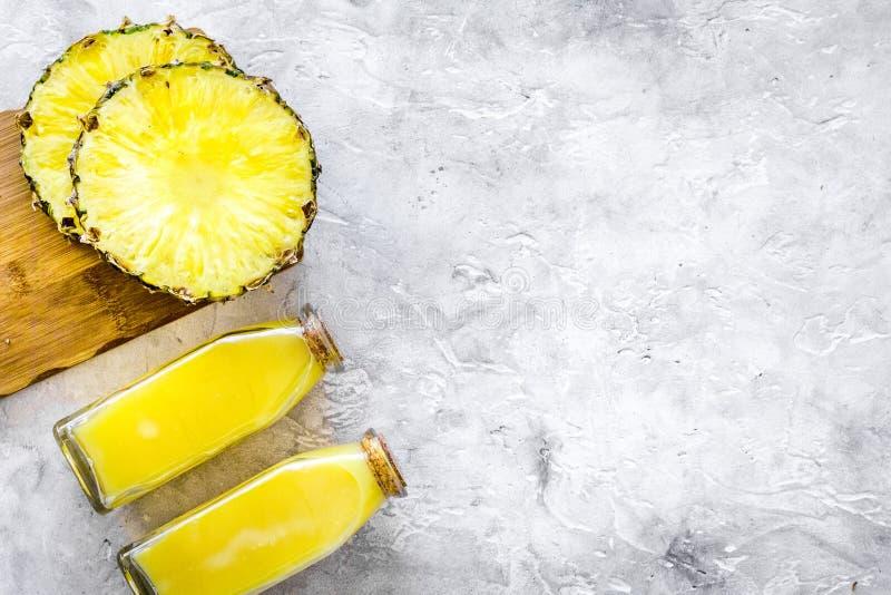Alkoholfreie Getränke Flasche mit Fruchtsaft nahe Ananasscheiben auf grauem copyspace Draufsicht des Hintergrundes lizenzfreies stockfoto