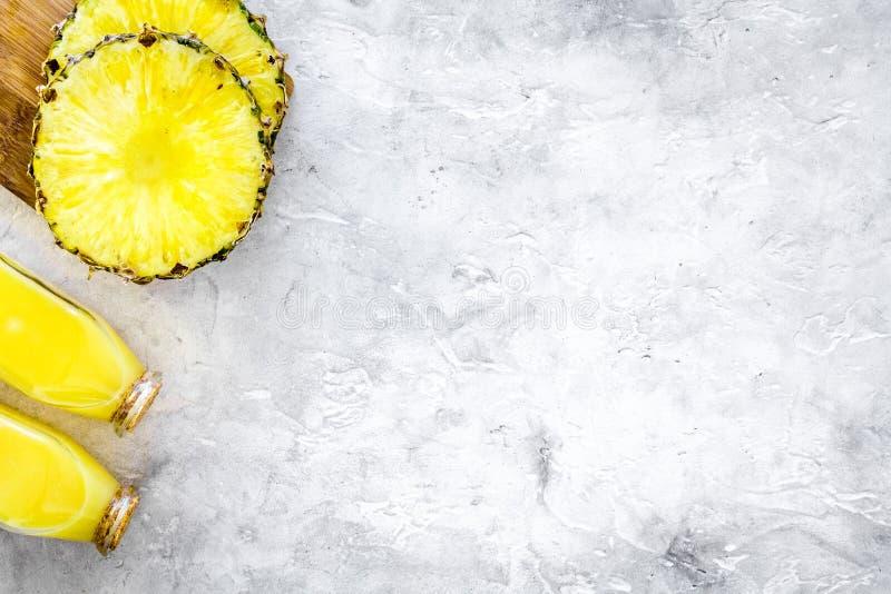 Alkoholfreie Getränke Flasche mit Fruchtsaft nahe Ananasscheiben auf grauem copyspace Draufsicht des Hintergrundes stockbilder