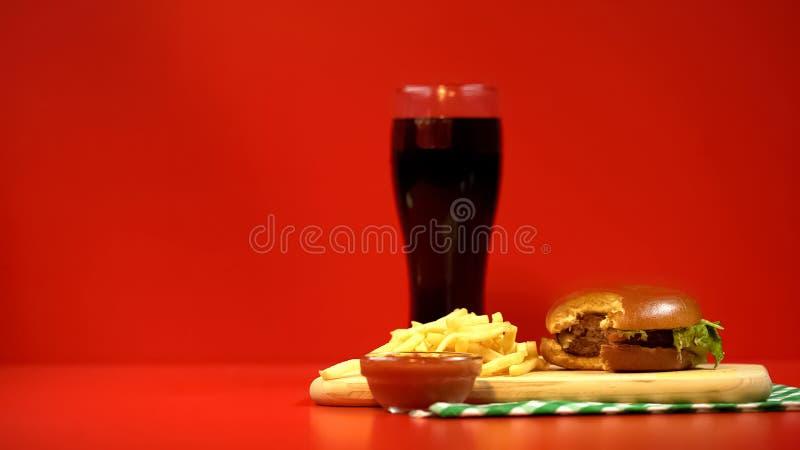 Alkoholfreies Getränk mit gebissenem Hamburger und Pommes-Frites, roter Hintergrund als Warnung lizenzfreie stockbilder