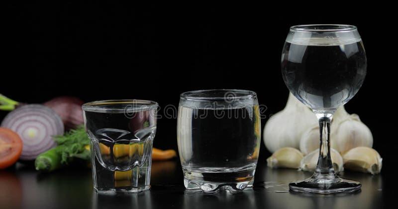 Alkoholgetränkwodka in den Schnapsgläsern Hintergrund mit Gem?se stockbild
