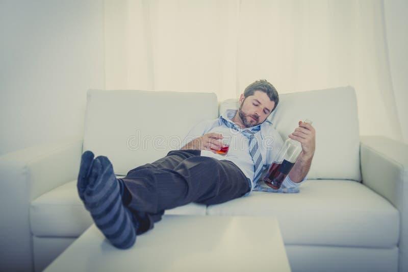 Alkoholiczny biznesmen w luźnym krawacie pijącym marnotrawił na leżance w domu obraz stock