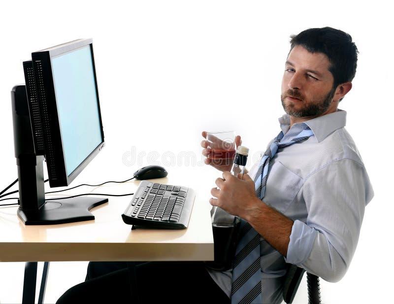 Alkoholiczny biznesowy mężczyzna pije whisky obsiadanie pijącego przy biurem z komputerem fotografia stock