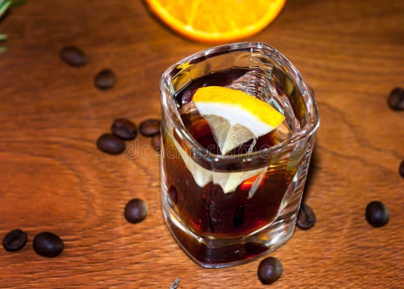 alkoholiczny koktajl w cristal szkle z cytryna plasterkami i kawowymi fasolami fotografia royalty free