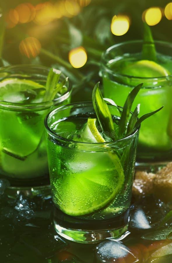 Alkoholiczny koktajl z wapno zieleni?, cytryna sok, trzcina cukier, soda, mia?d?y? l?d i estragonowych li?cie, czarny t?o, selekc zdjęcie stock