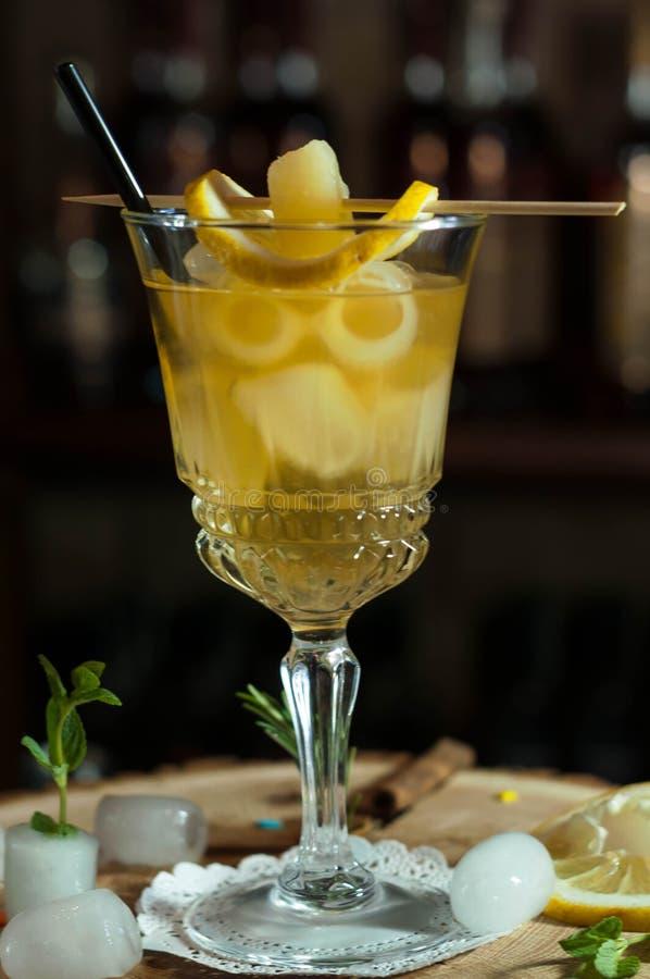Alkoholiczny napój w szkle z słomą, cytryna plasterkami i ziele czarnymi pije, zdjęcia royalty free