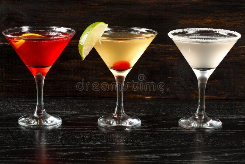 Alkoholische Cocktailreihe auf hölzernen backgroundks, bunte Parteigetränke Stellen Sie von den klassischen Cocktails ein stockfotografie