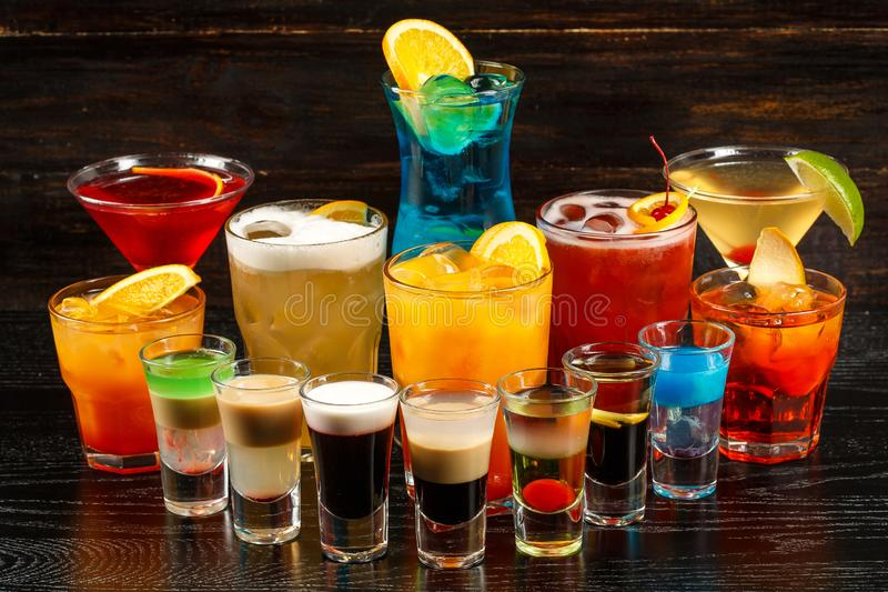 Alkoholische Cocktailreihe auf hölzernen backgroundks, bunte Parteigetränke Stellen Sie von den klassischen Cocktails ein lizenzfreie stockbilder