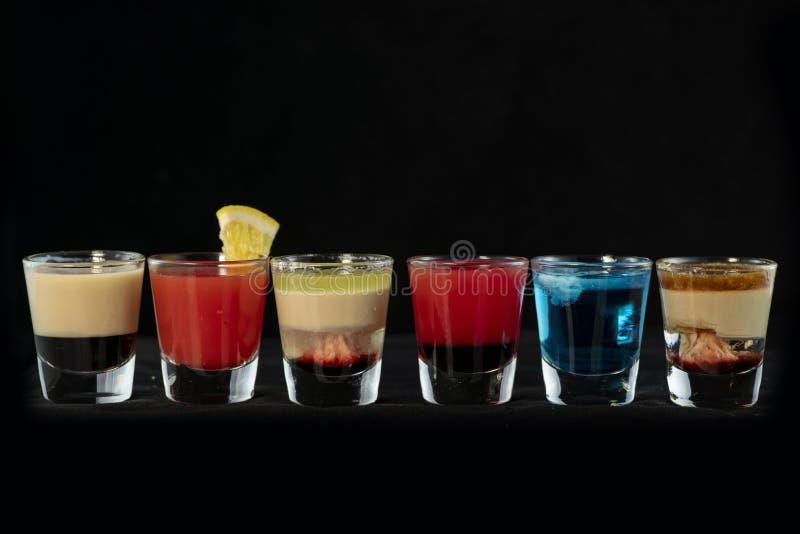 Alkoholische Cocktailschüsse der Mischung zusammen mit lokalisiertem schwarzem Hintergrund lizenzfreies stockbild