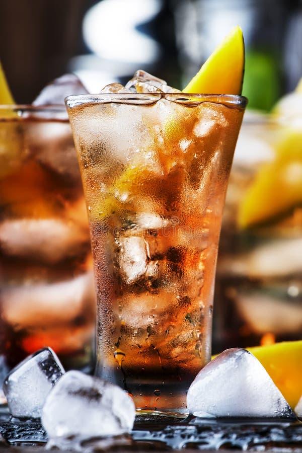 Alkoholischer Cocktail mit Mango, Cranberries, Kalkeis, zerdrücktem Eis und Likor, dunkelhölzerne Bartheke Hintergrund, selektiv lizenzfreies stockfoto