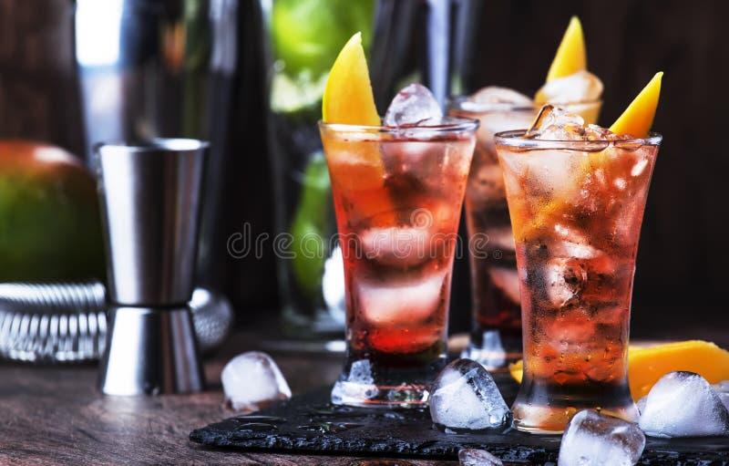 Alkoholischer Cocktail mit Mango, Cranberries, Kalkeis, zerdrücktem Eis und Likor, dunkelhölzerne Bartheke Hintergrund, selektive stockbilder