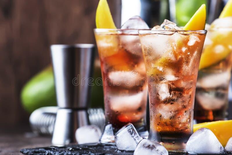 Alkoholischer Cocktail mit Mango, Cranberries, Kalkeis, zerdrücktem Eis und Likor, dunkelhölzerne Bartheke Hintergrund, selektive stockbild