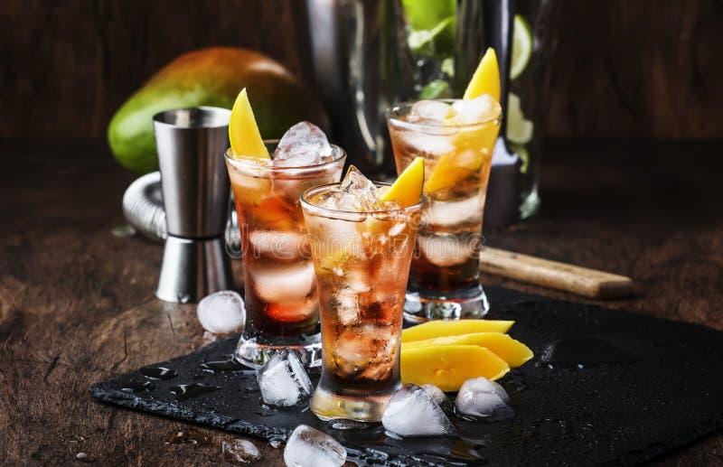 Alkoholischer Cocktail mit Mango, Cranberries, Kalkeis, zerdrücktem Eis und Likor, dunkelhölzerne Bartheke Hintergrund, selektive stockfotos