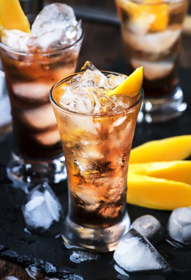 Alkoholischer Cocktail mit Mango, Cranberries, Kalkeis, zerdrücktem Eis und Likor, dunkelhölzerne Bartheke Hintergrund, selektive stockfoto