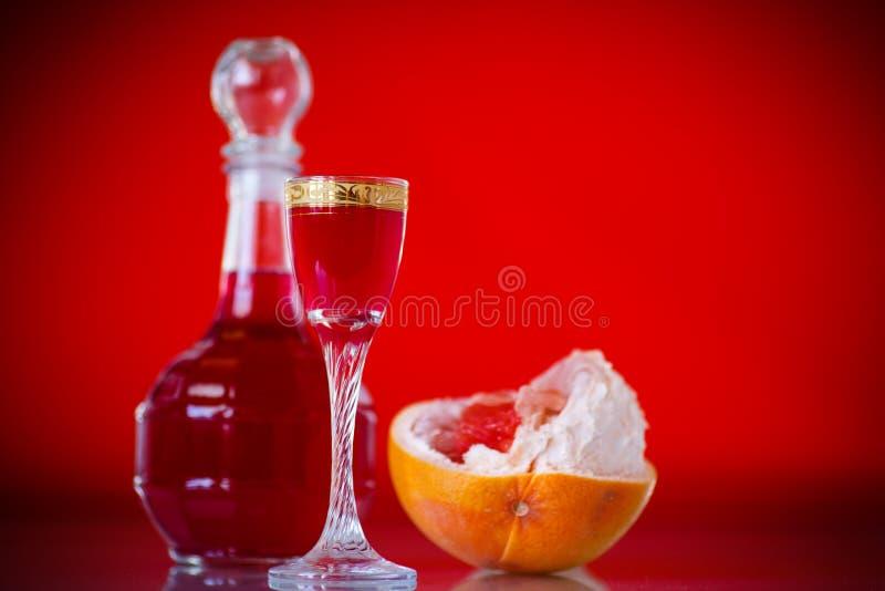 Alkoholischer Likör der süßen Pampelmuse im Dekantiergefäß mit einem Glas stockfotografie