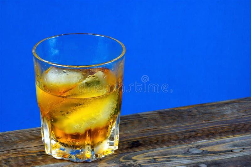 Alkoholisches Getr?nk mit Eis auf die Holztischoberseite, blauen Hintergrund Starkes aromatisches alkoholisches Getr?nk, von den  stockbild