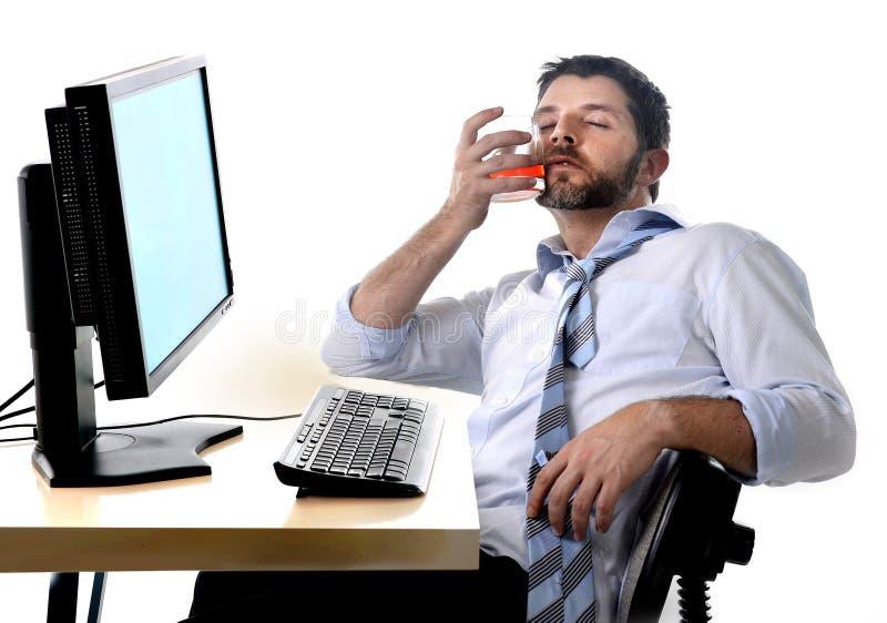 Alkoholiserad affärsman som dricker whiskysammanträde som drickas på kontoret med datoren arkivfoto
