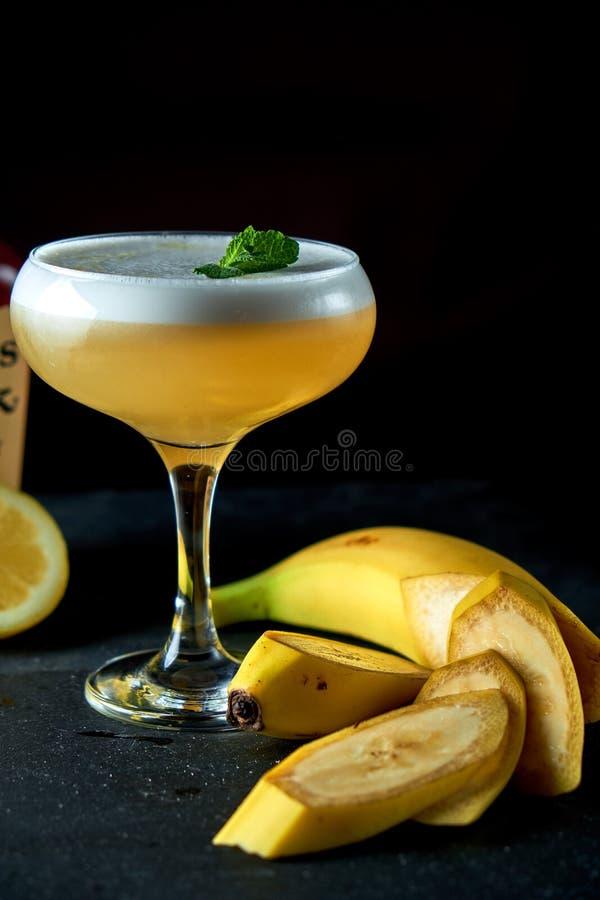 Alkoholiserad coctail för banan i ett exponeringsglas, svart bakgrund, stång, royaltyfri foto