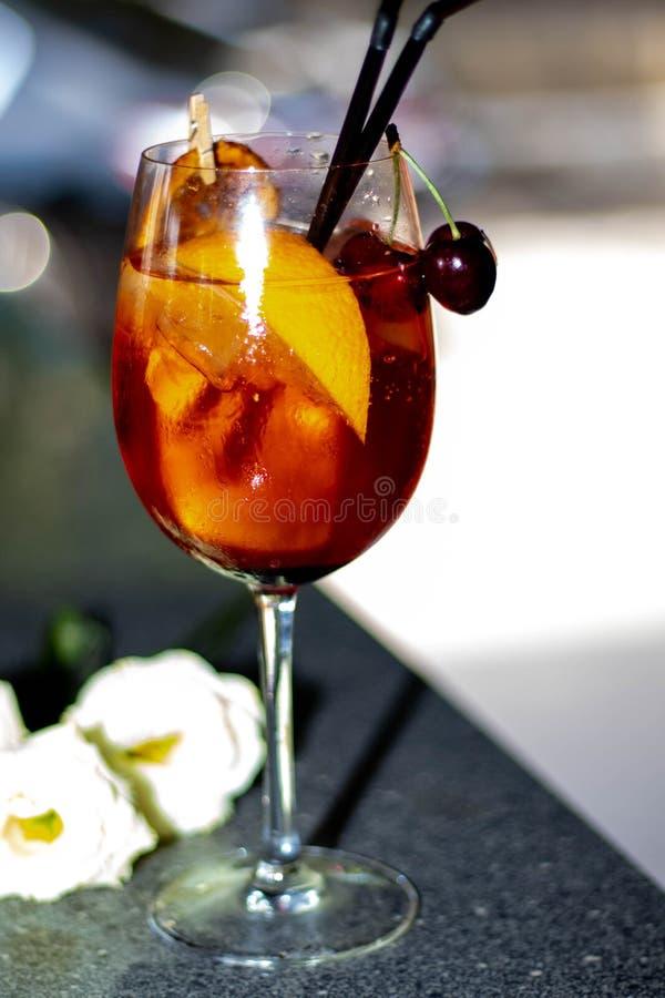 Alkoholiserad coctail i ett genomskinligt exponeringsglas på ett tunt ben royaltyfri fotografi