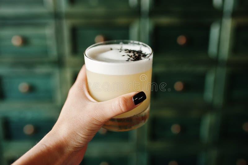 Alkoholiserad coctail i exponeringsglas förestående av bartendern royaltyfria foton