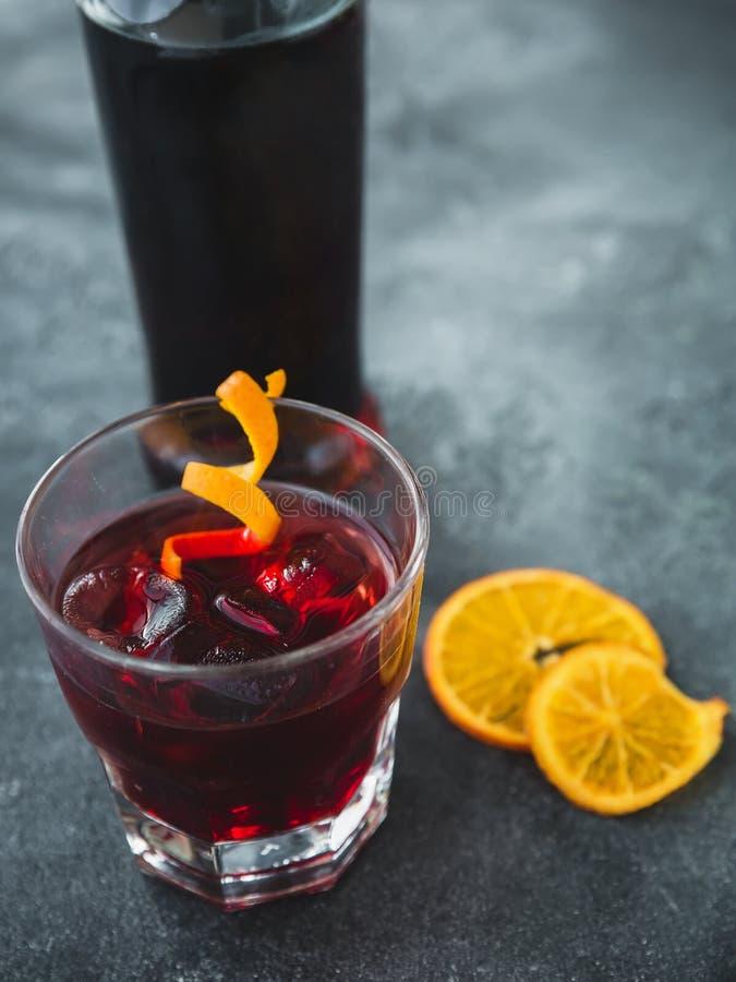 Alkoholiserad coctail med apelsinen Alkoholiserad kall drink i stång och glasflaska royaltyfria bilder