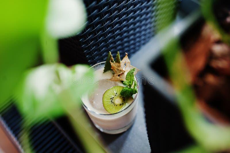 Alkoholiserad coctail med kiwin i exponeringsglas på tabellen royaltyfria bilder
