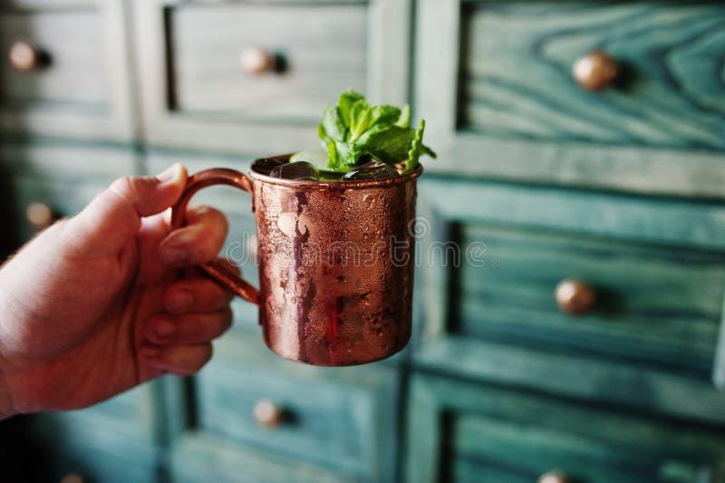 Alkoholiserad coctail med is, mintkaramellen och limefrukt i bronskopp på handen royaltyfria foton