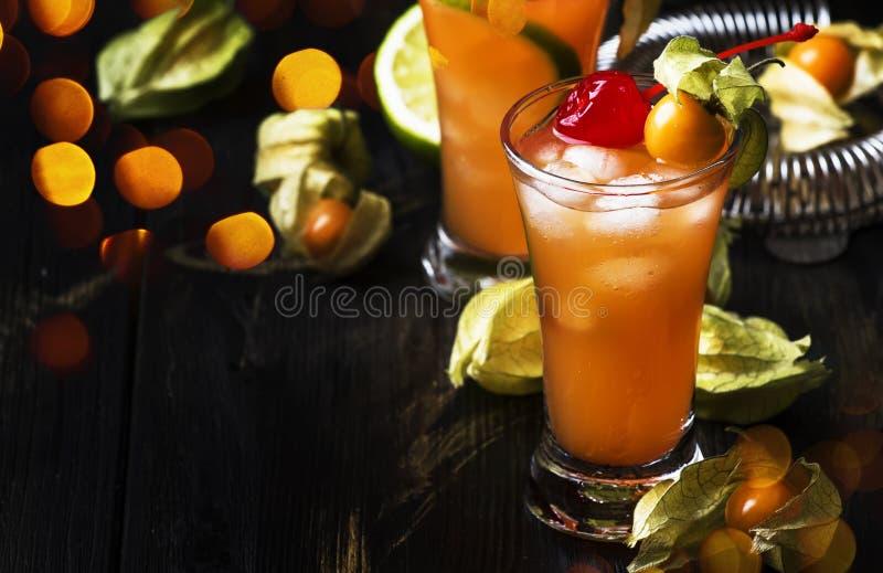 Alkoholiserad coctail med vodka, lik?r, bitterhet, limefruktfruktsaft som dekoreras med physalisen och maraschinok?rsb?r, m?rk ba arkivbild