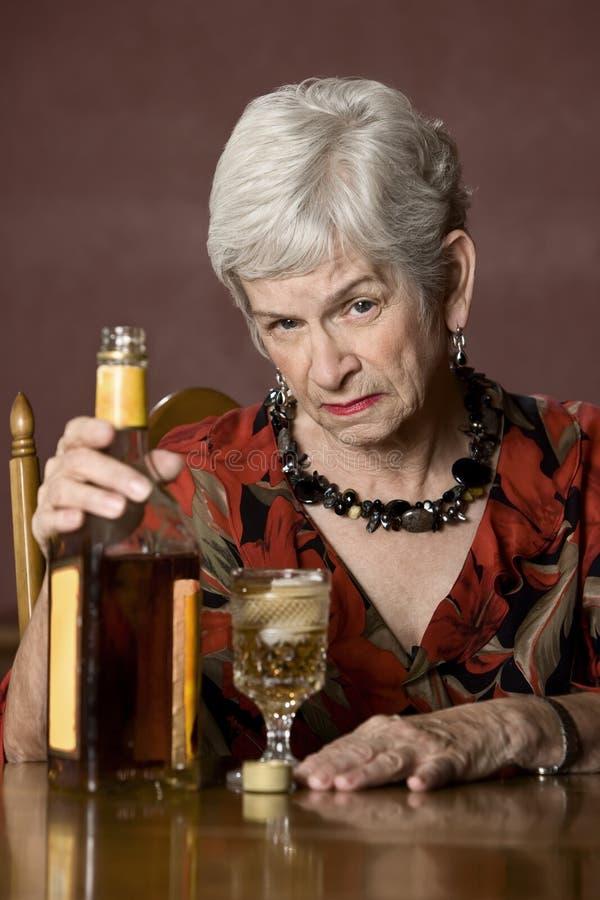 alkoholiserad elderykvinna arkivfoto